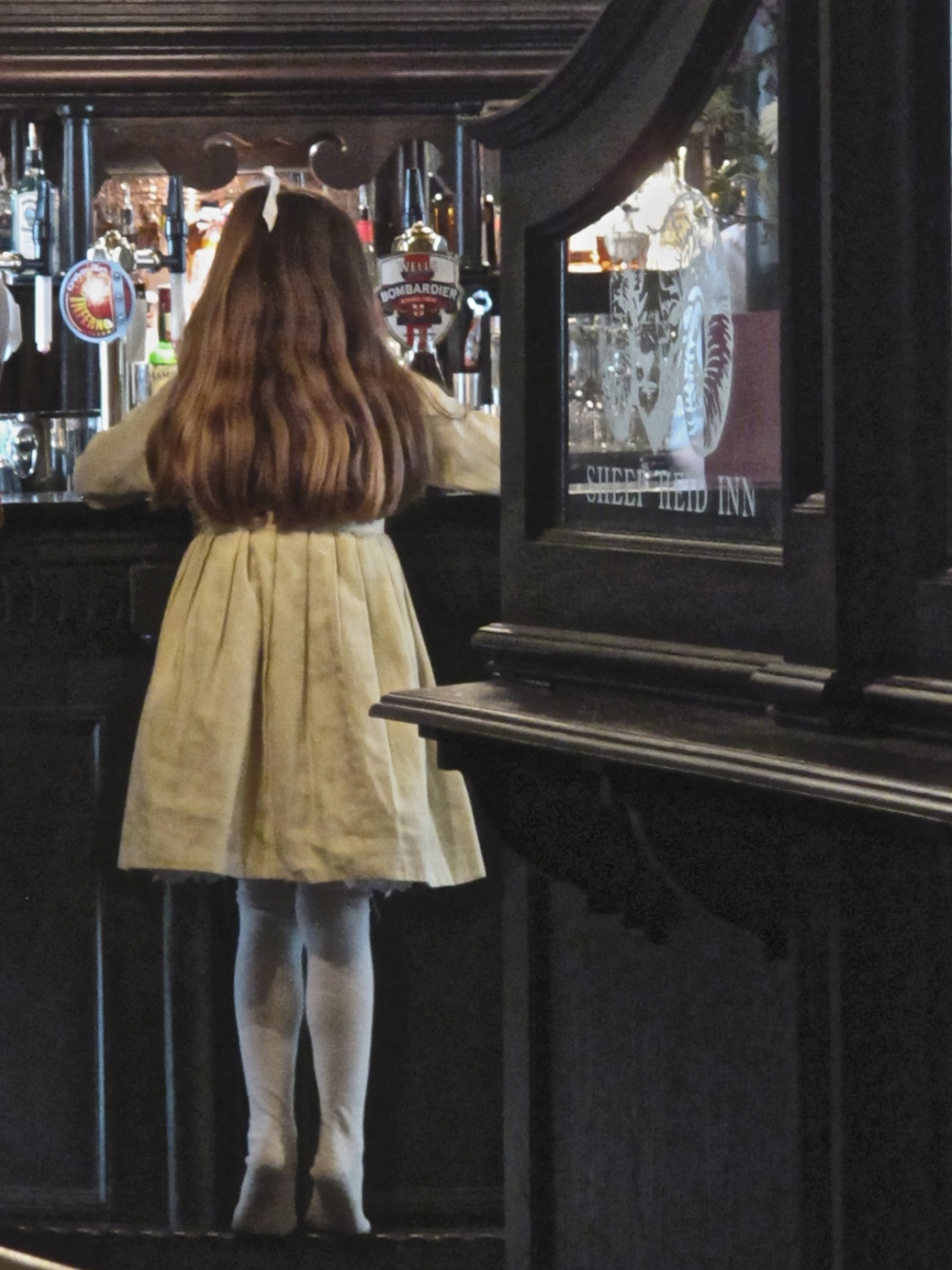 Young girl standing on tiptoe at the Sheep Hied Inn, Edinburgh.