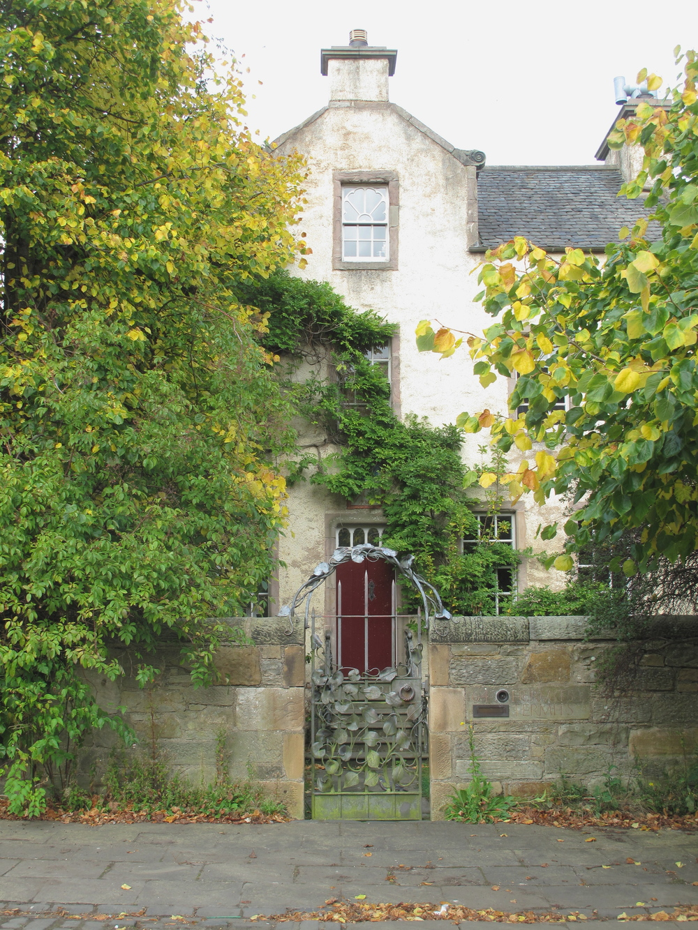Small Scottish house with a red door in autumn.