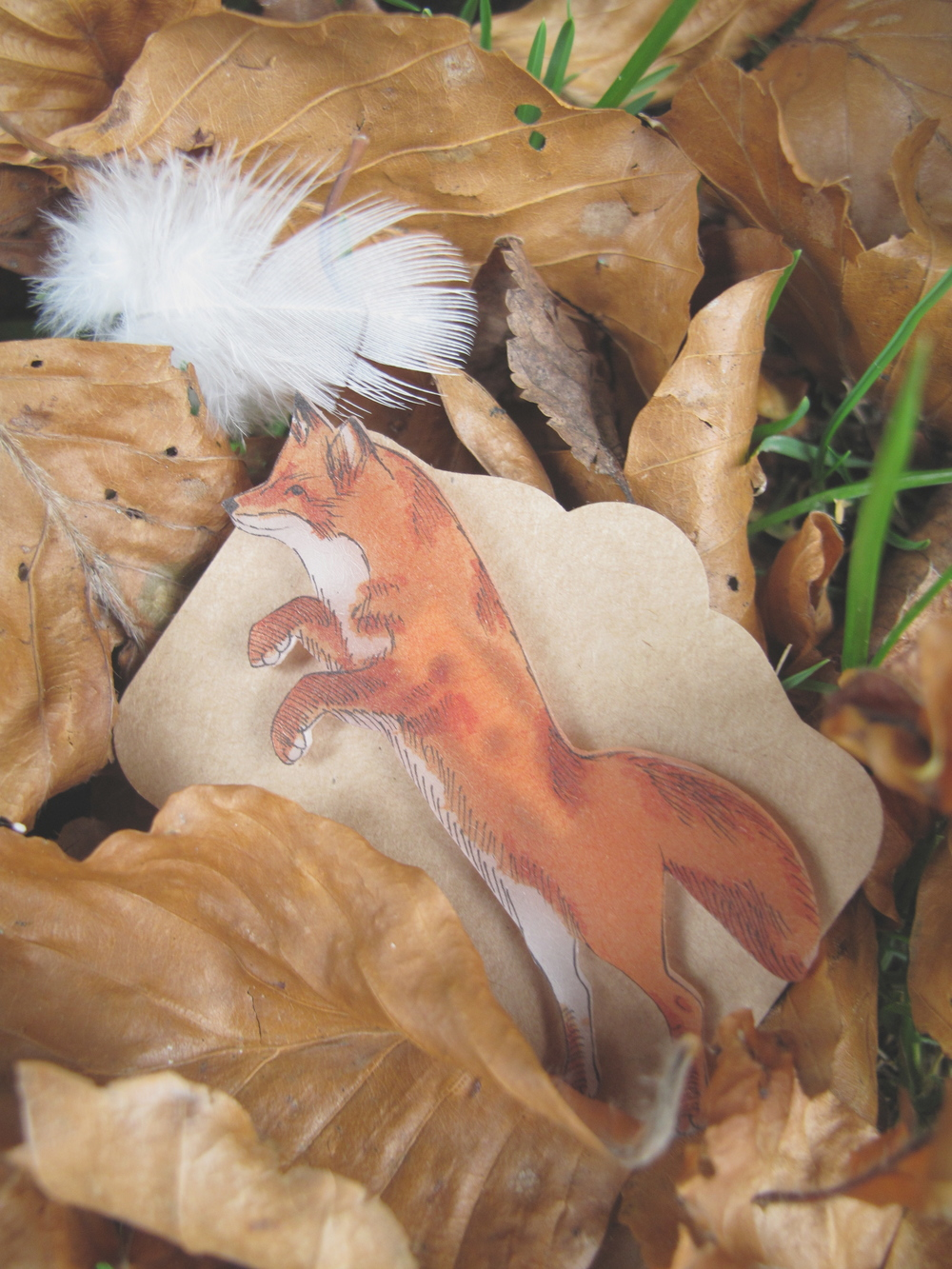 Handmade fox brooch in autumn leaves.