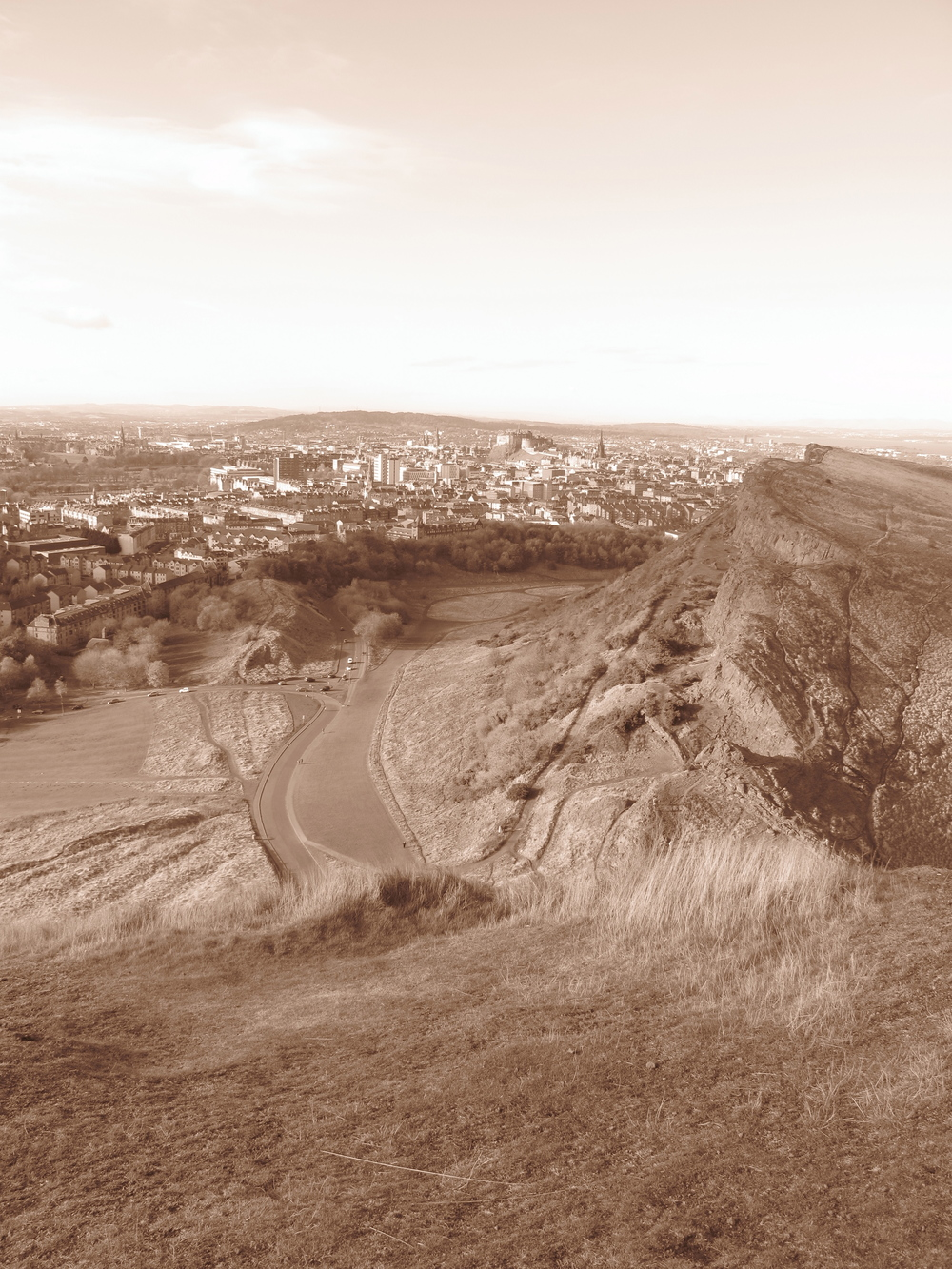 Holyrood Park cliffs and view of the city of Edinburgh - in sepia tones.