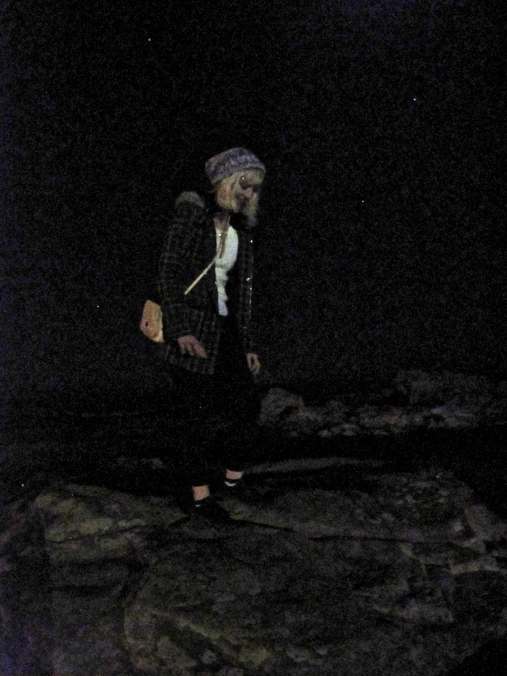 Jamie climbing on rocks at the beach in St Andrews at night.