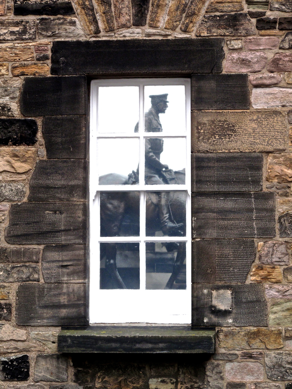 Window reflection of an equestrian statue in Edinburgh Castle.