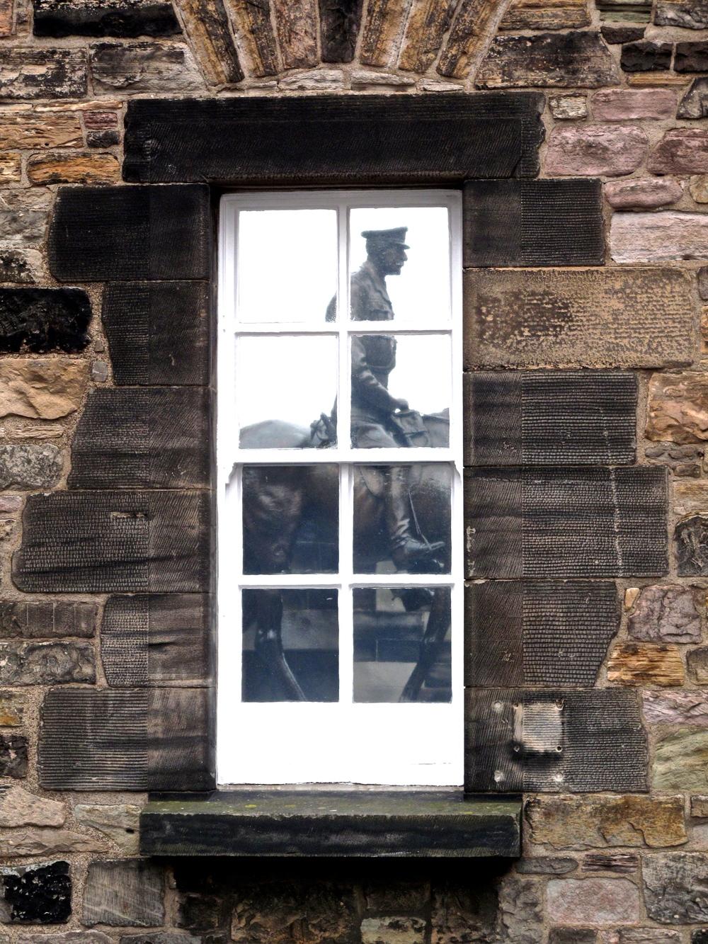 Window reflection of an equestrian statue in Edinburgh Castle.