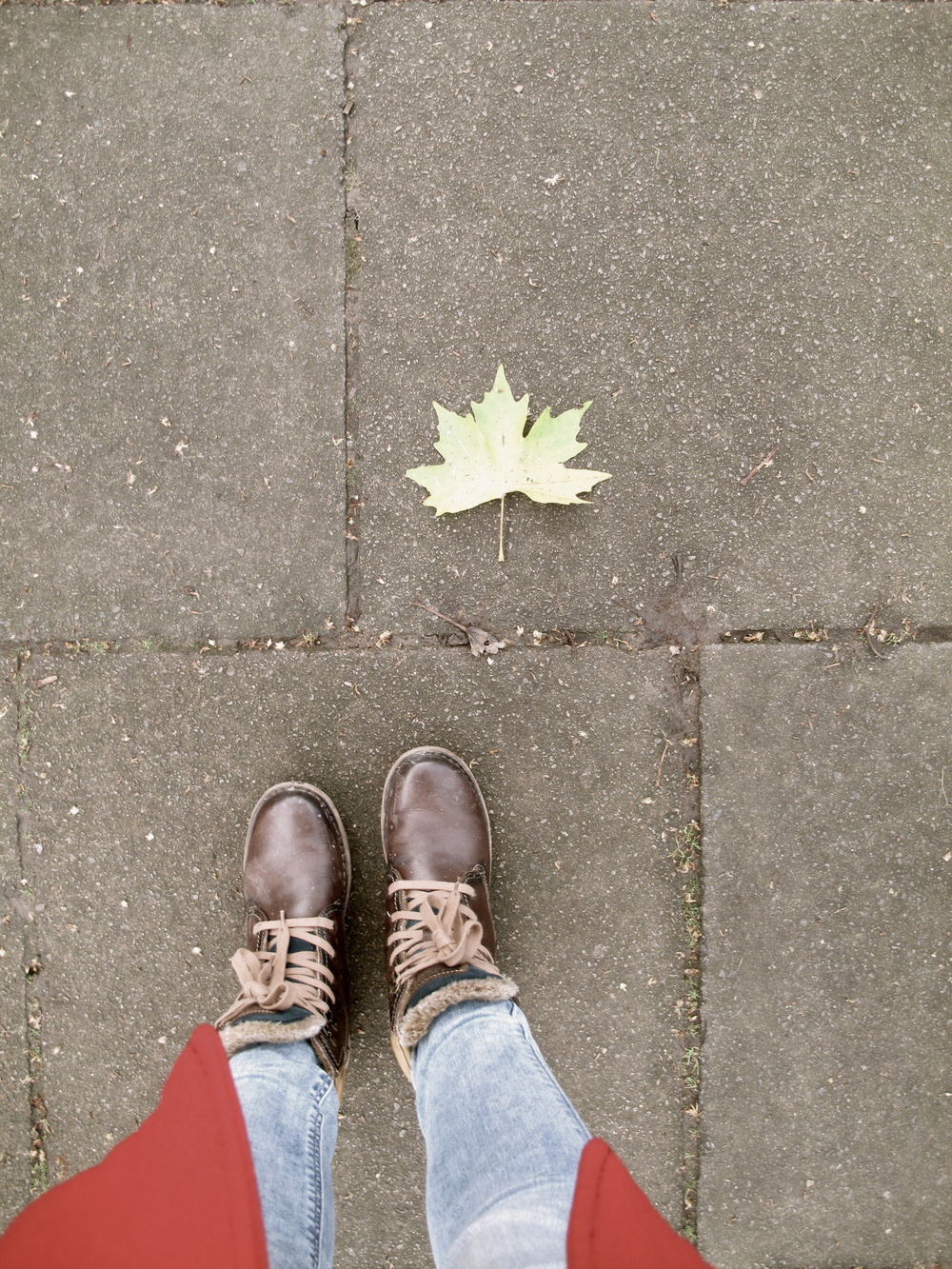 Autumn leaf and winter boots on the stone path.
