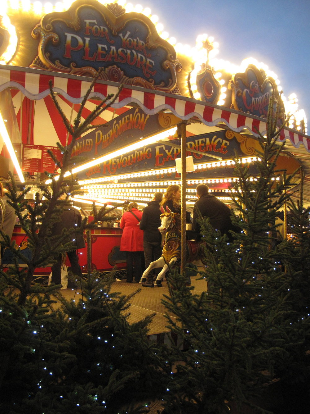 Merry go round with bright stripes at night, in the Edinburgh christmas market.