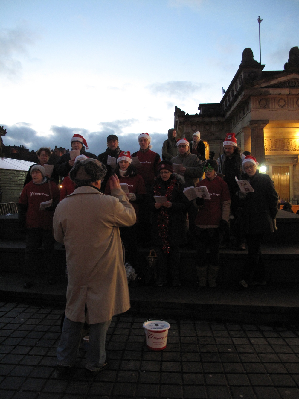 Carol singing choir at the Edinburgh Christmas Market at night.