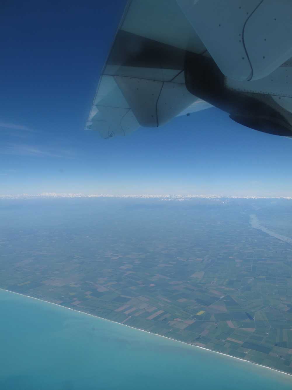 Flying out of New Zealand - plane wing, blue seas and rolling countryside.