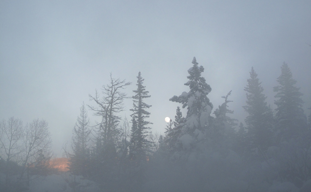 Full moon seen through the steam and snow at Strawberry Hot Springs.
