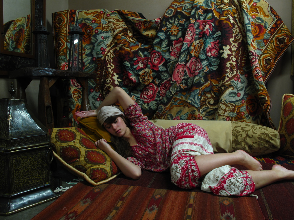 Matisse style photoshoot - oriental harem girl reclining in cushions.