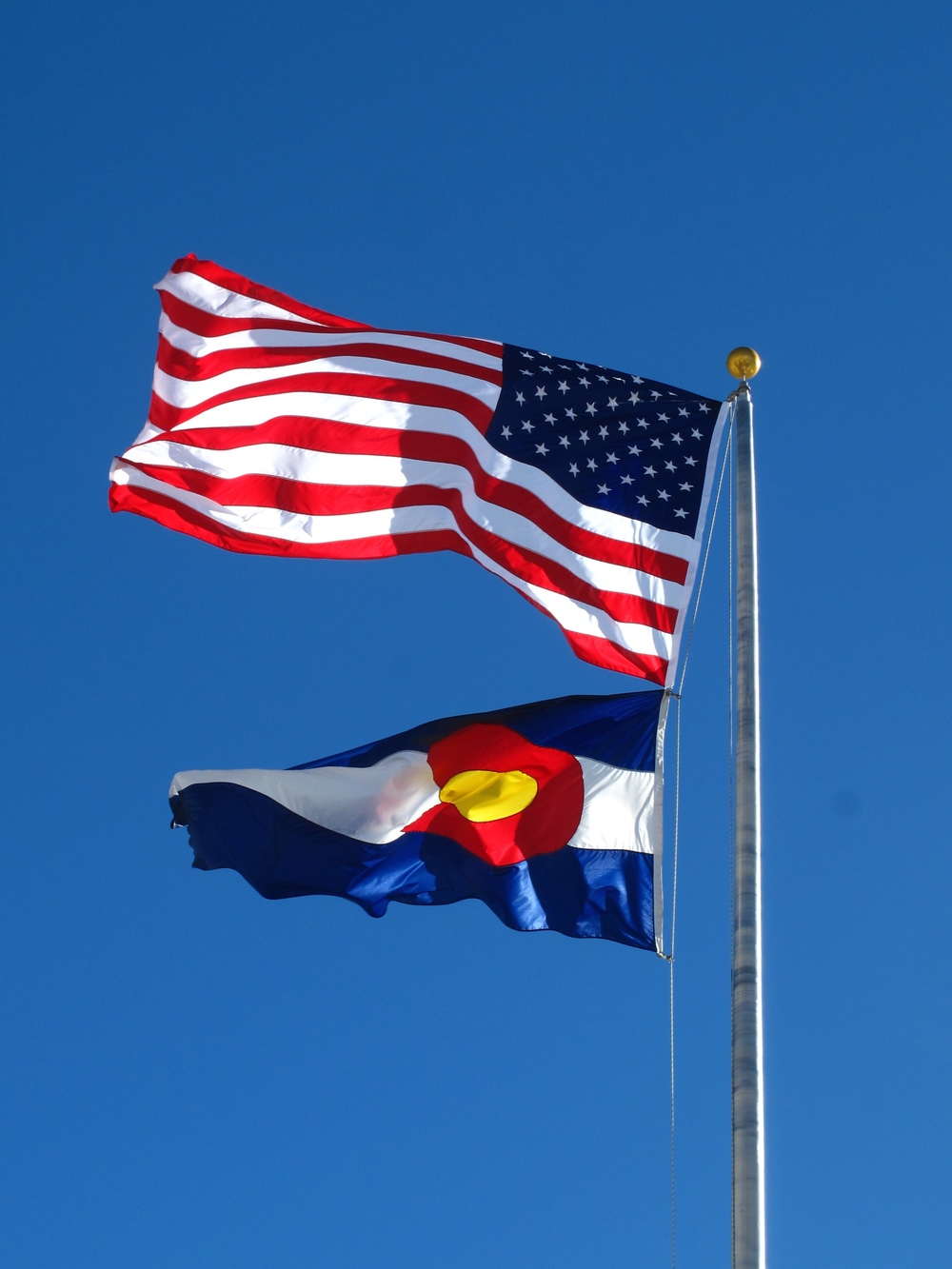 The American flag and the Colorado flag flying in the breeze.
