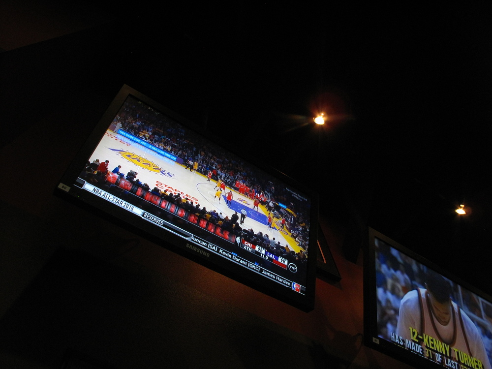 TV screens set up in a buffalo wild wings restaurant, playing sports channels.