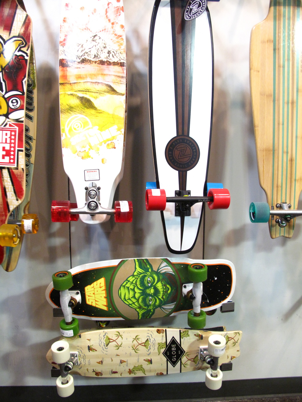 A colourful rack of long board skateboards.