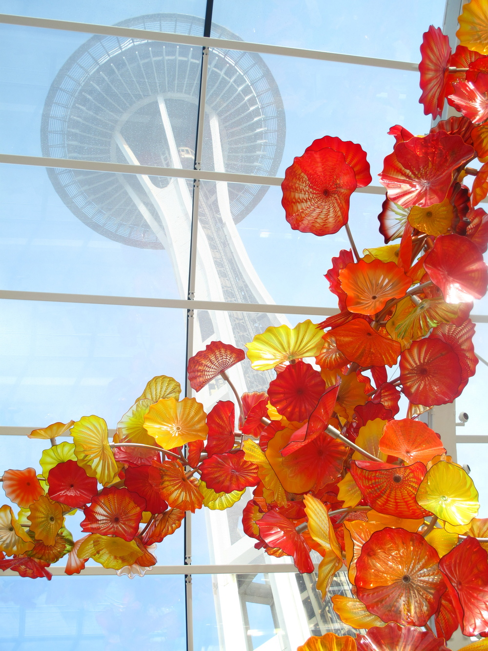 The Seattle Space Needle, seen from the Chihuly Museum - glass flowers and blue sky.