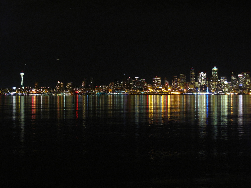 The Space Needle and Seattle lights skyline seen from Alki Beach at night.