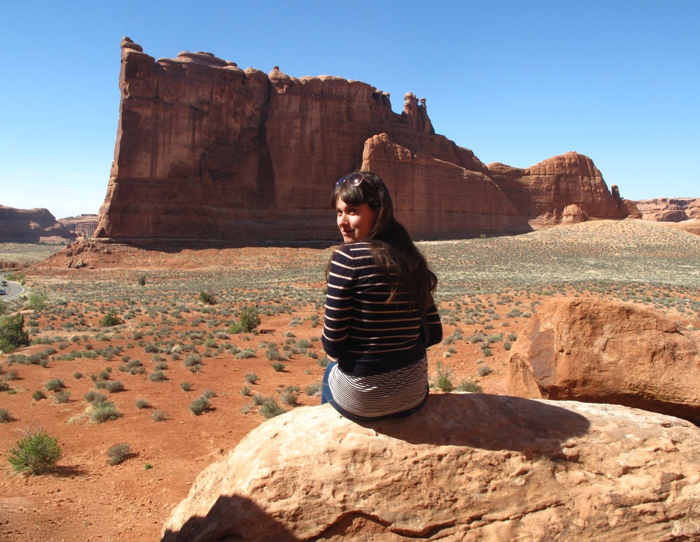 Sitting on a rock in front of the Courthouse Towers, in Arches National Park.