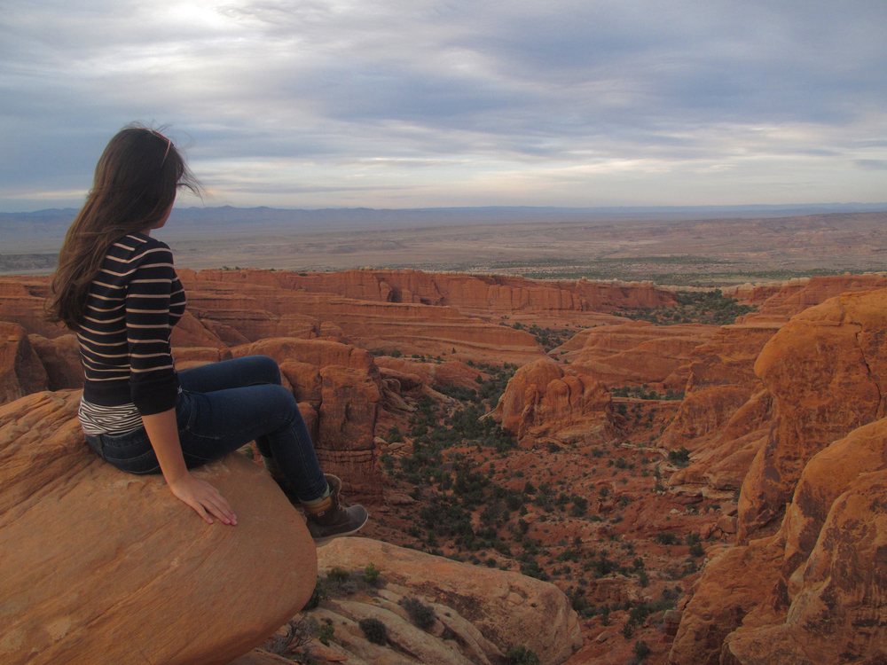 Sitting on top of Arches National Park ledge, looking over the park.