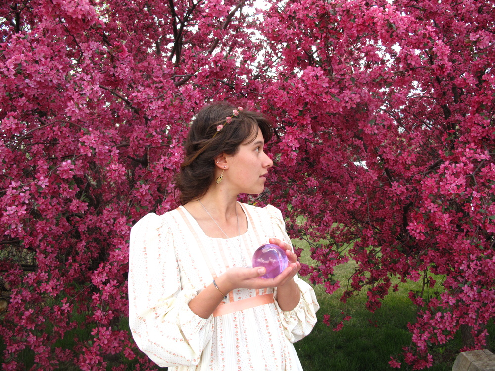Zoe fairy, with a crystal ball, under the pink blossoms trees.