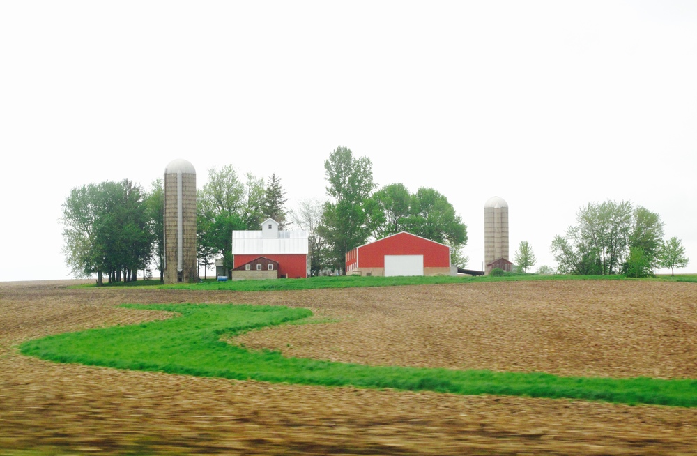 A red barn and silos on a farm in Lanark Illinois.