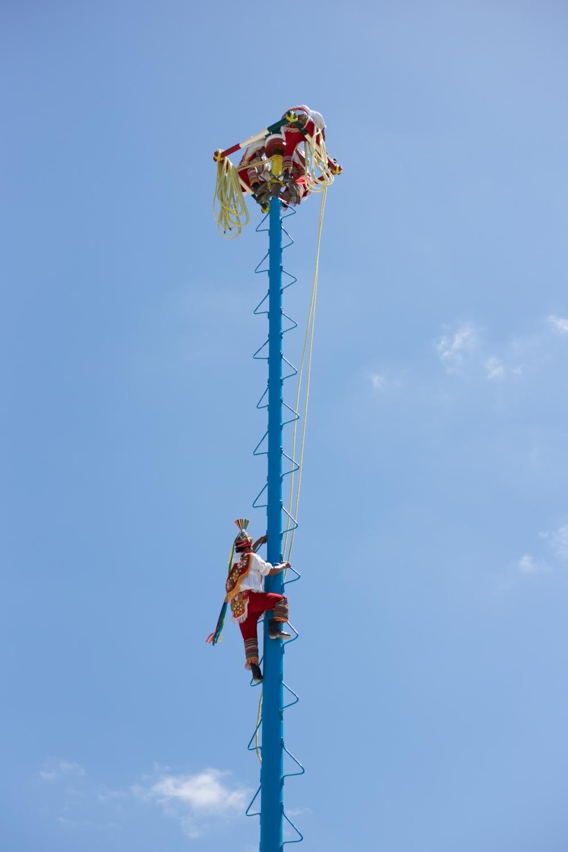 Voladores de Papantla in Cancun - men climbing a tall pole in a mexican ceremony.