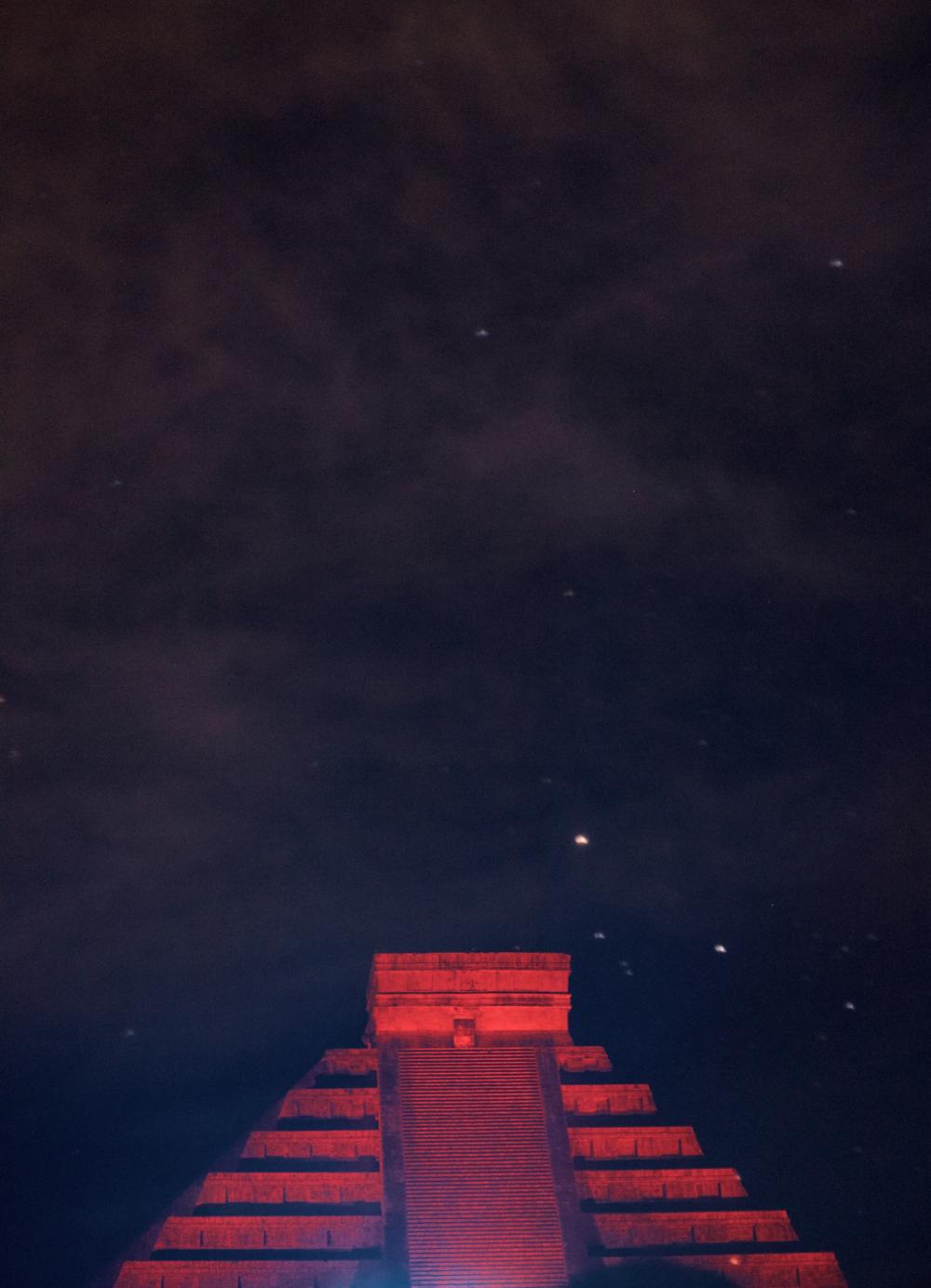 Chichen Itza under the stars at night - lit up red.