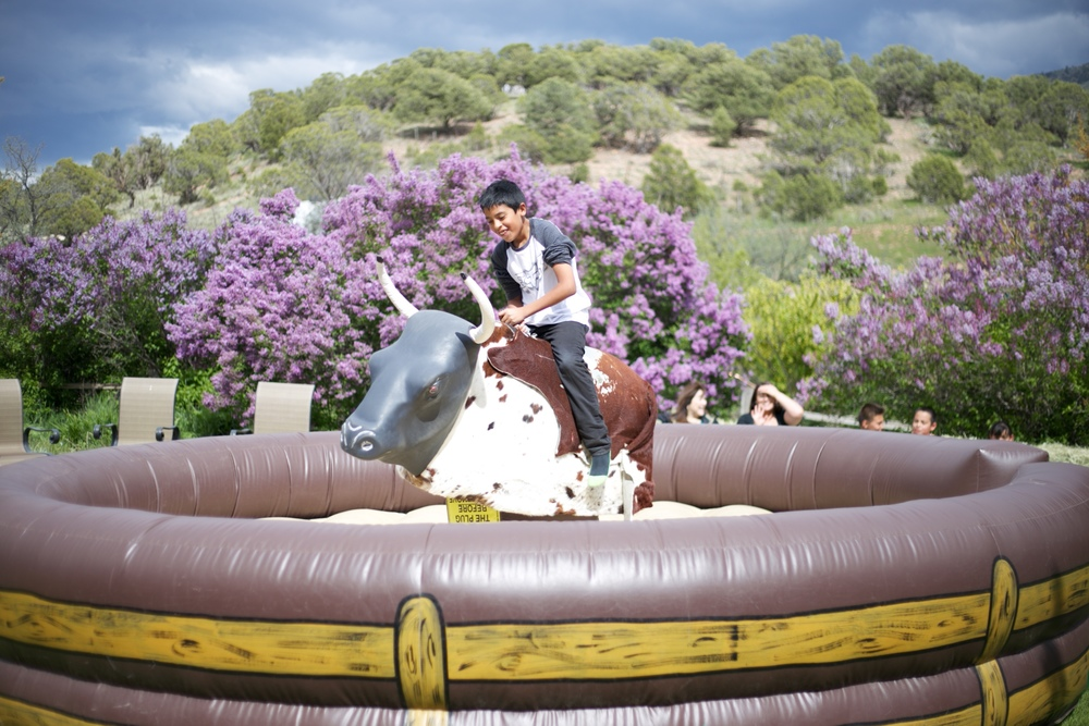 A young Mexican boy on a mechanical bull, at a Mexican Party.