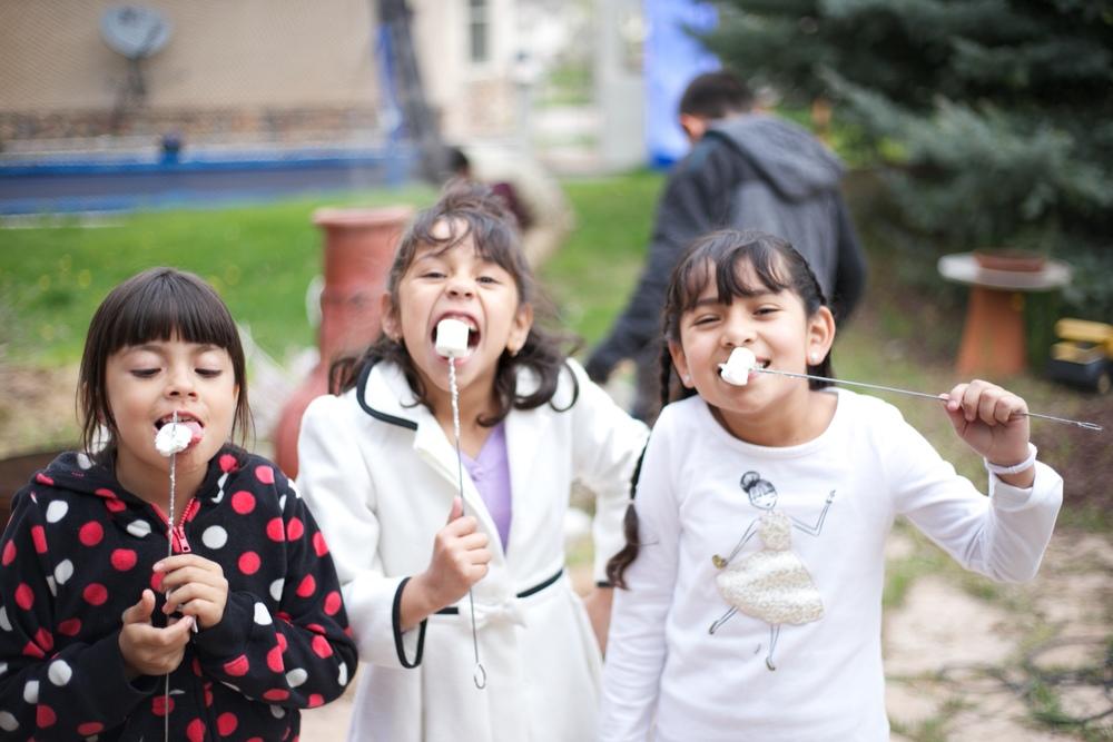 Sofia, Andrea and Camila eating roasted marshmellows.