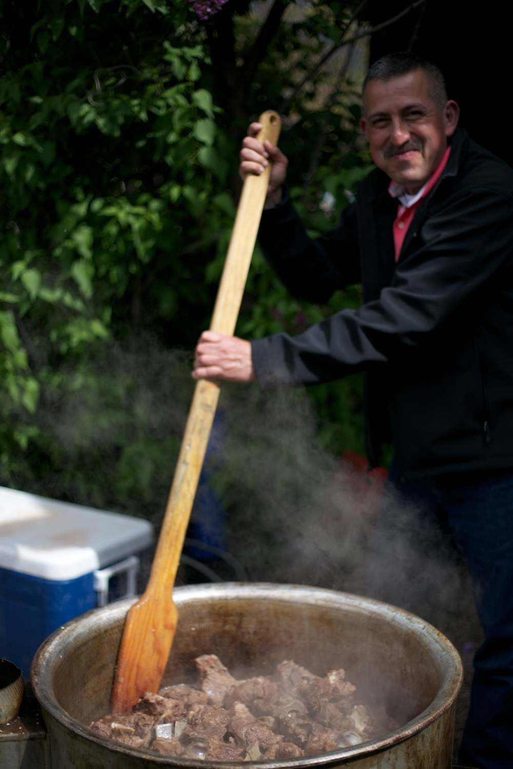 Bari stirring the carne cooking in a giant pot in the ground.