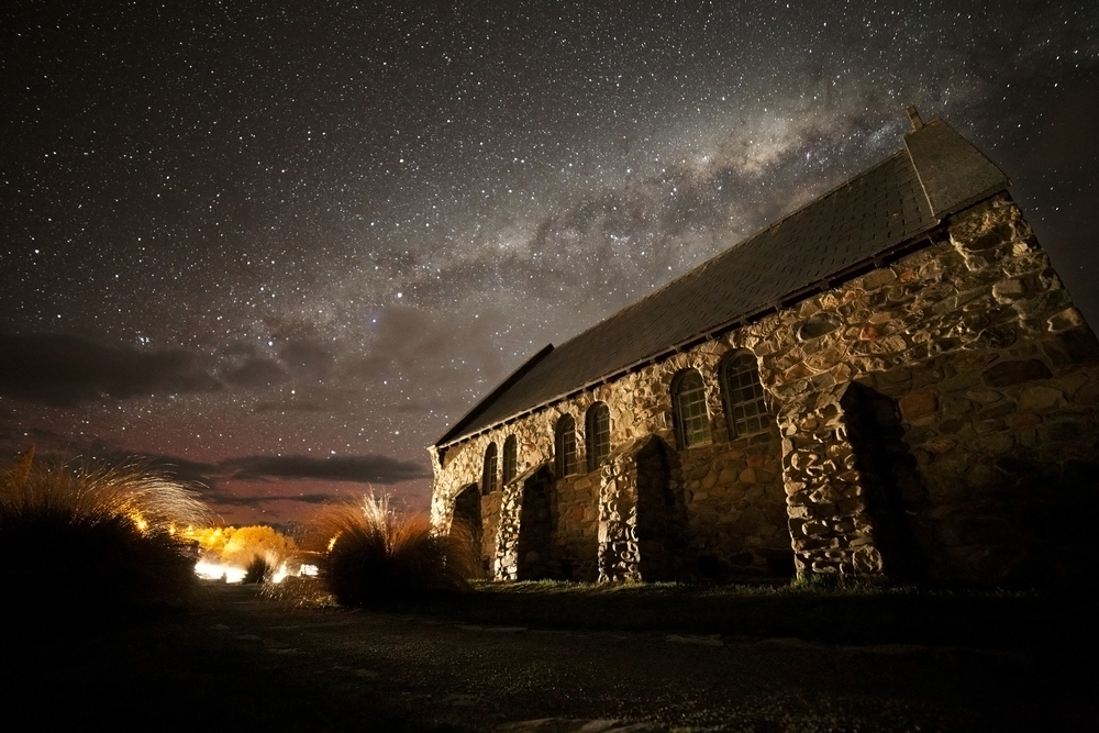 The Church of the Good Shepherd and a purple tinged milky way with city lights.