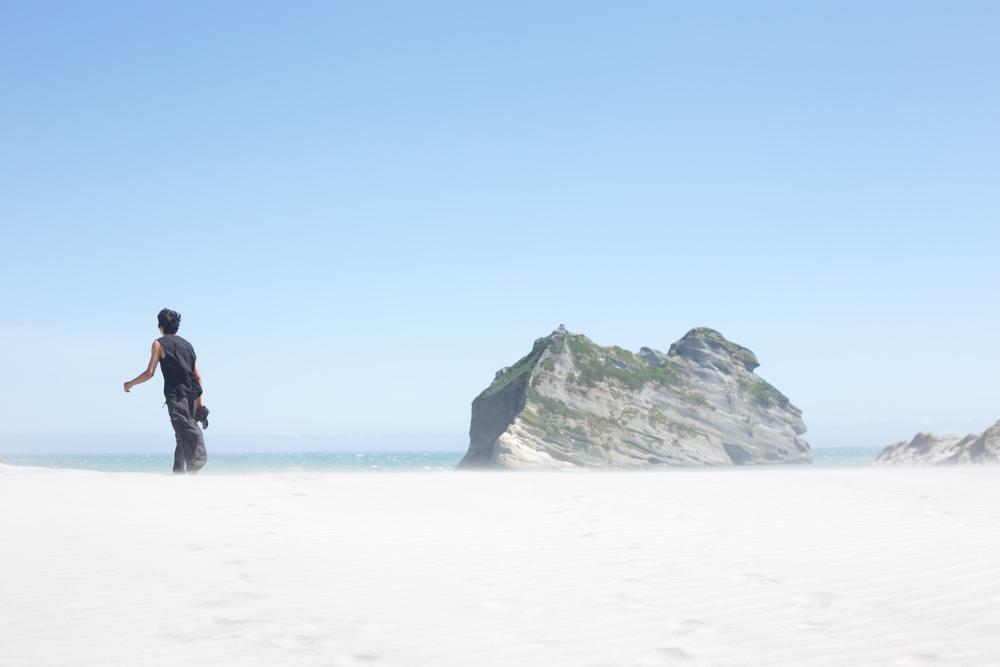 Oliver walking on the shifting sands at Wharariki Beach.