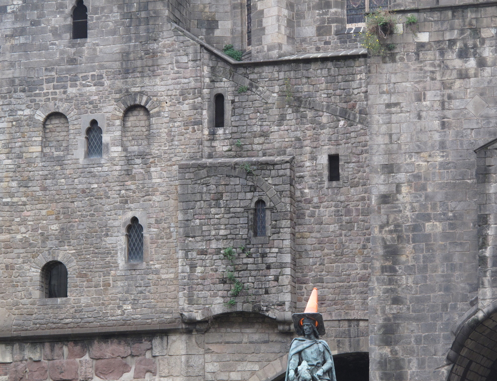 Cone head - a traffic cone on top of an equestrian statue.