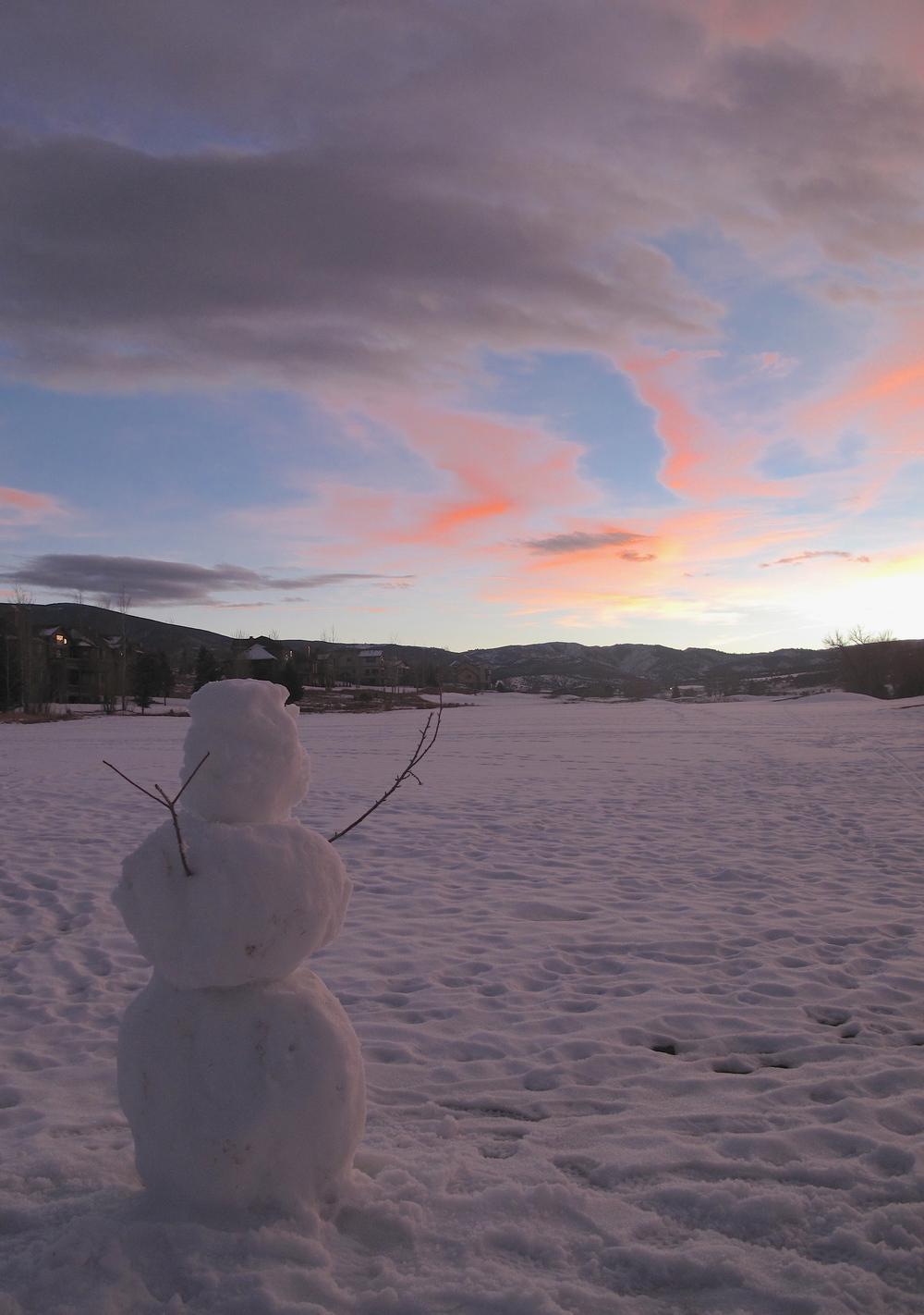 A snowman under a sunset.