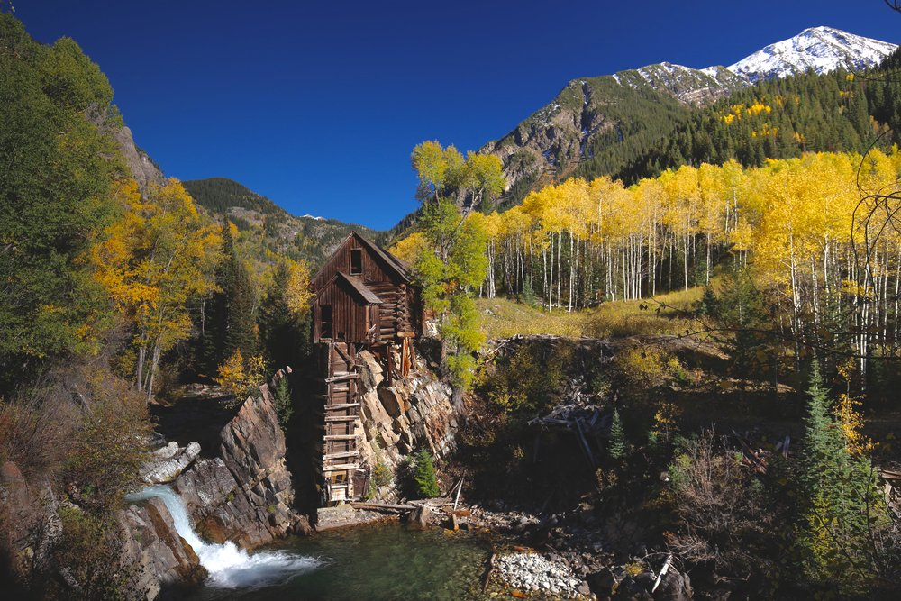The Crystal Mill in Fall, with yellow leaves and blue waterfall.