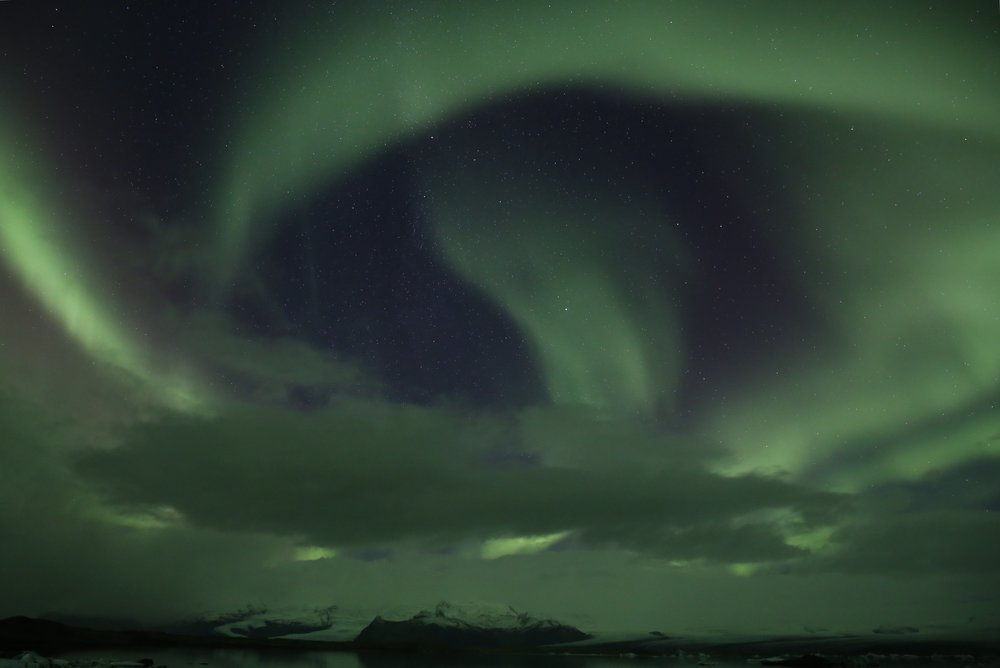 Swirling green northern lights and starry sky Iceland