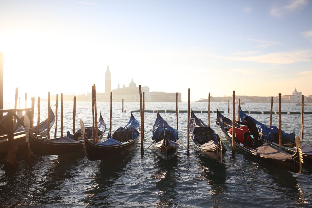 Gondolas bobbing in the water at sunrise with a view of San Giorgio Maggiore.