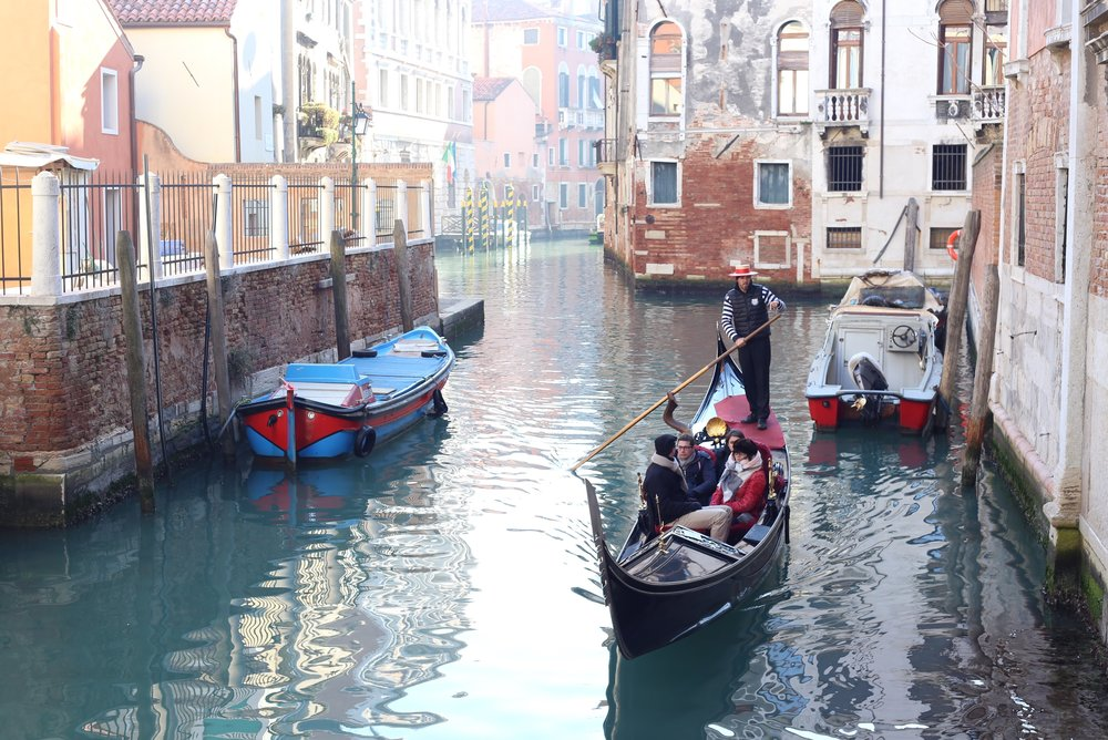 A gondola drifts in still waters.