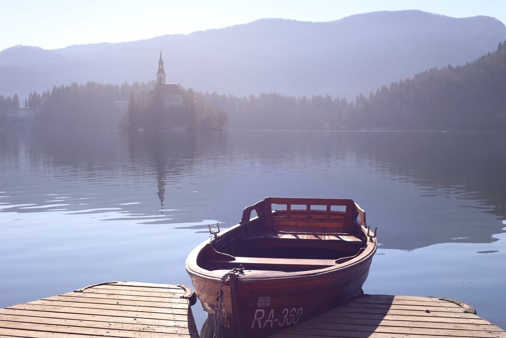 A boat sits by the dock, with Bled island in the background.