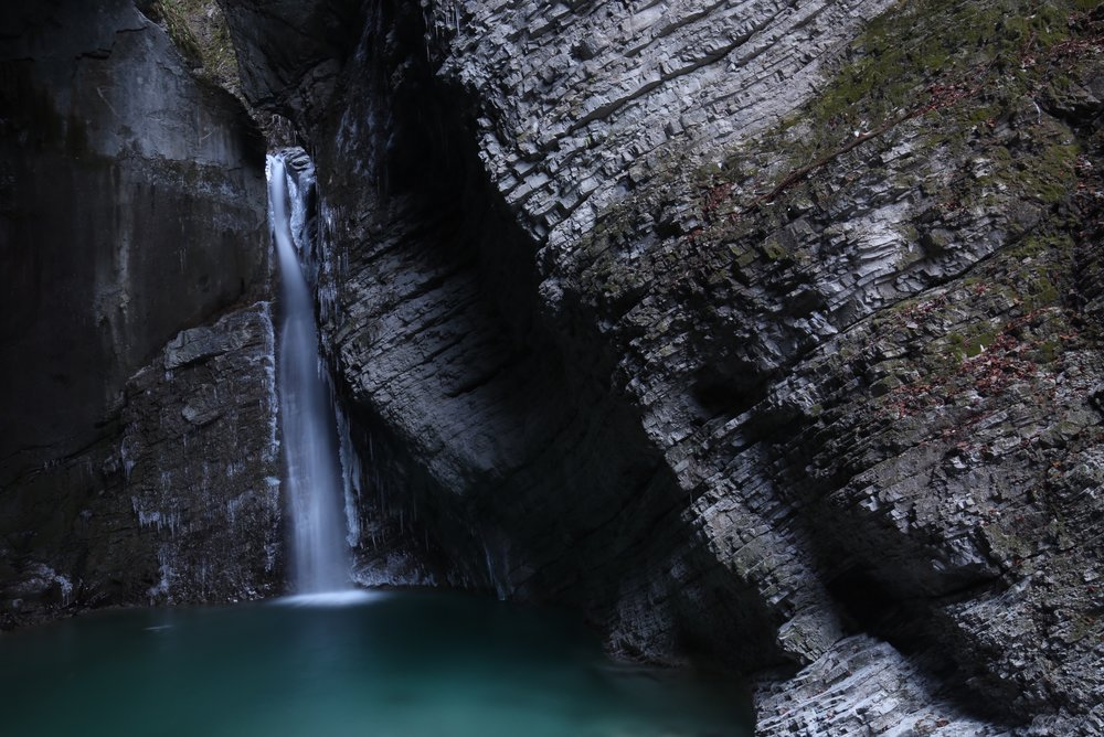 Kozjak waterfall rushes into a blue pool.