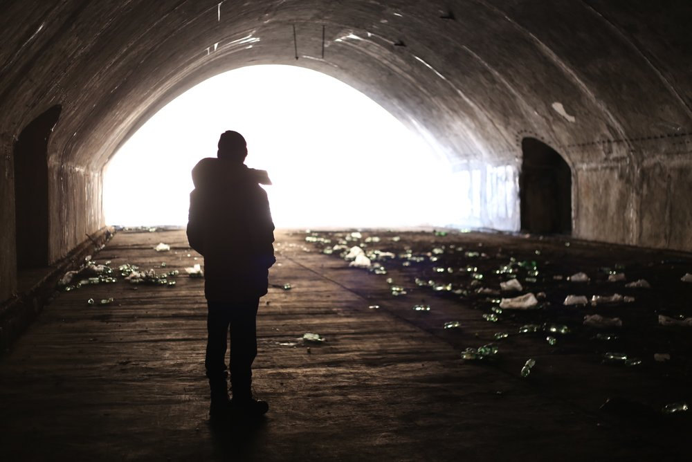 Oliver stands amongst glistening water bottles in the abandoned airplane hangar of Mostar.