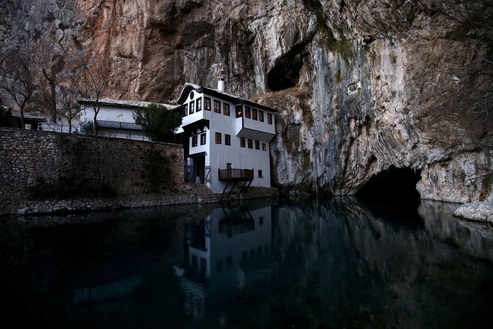 Blagaj Tejika - a small islamic center sits above the dark waters of the spring at sunset.
