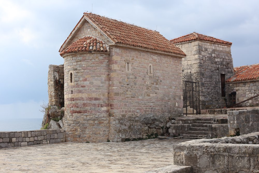 Budva town walls by the sea - with pink stone towers.