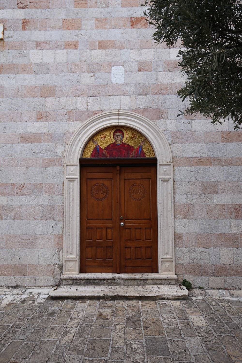 A stone wall, a wooden door, a mosaic and an olive branch.