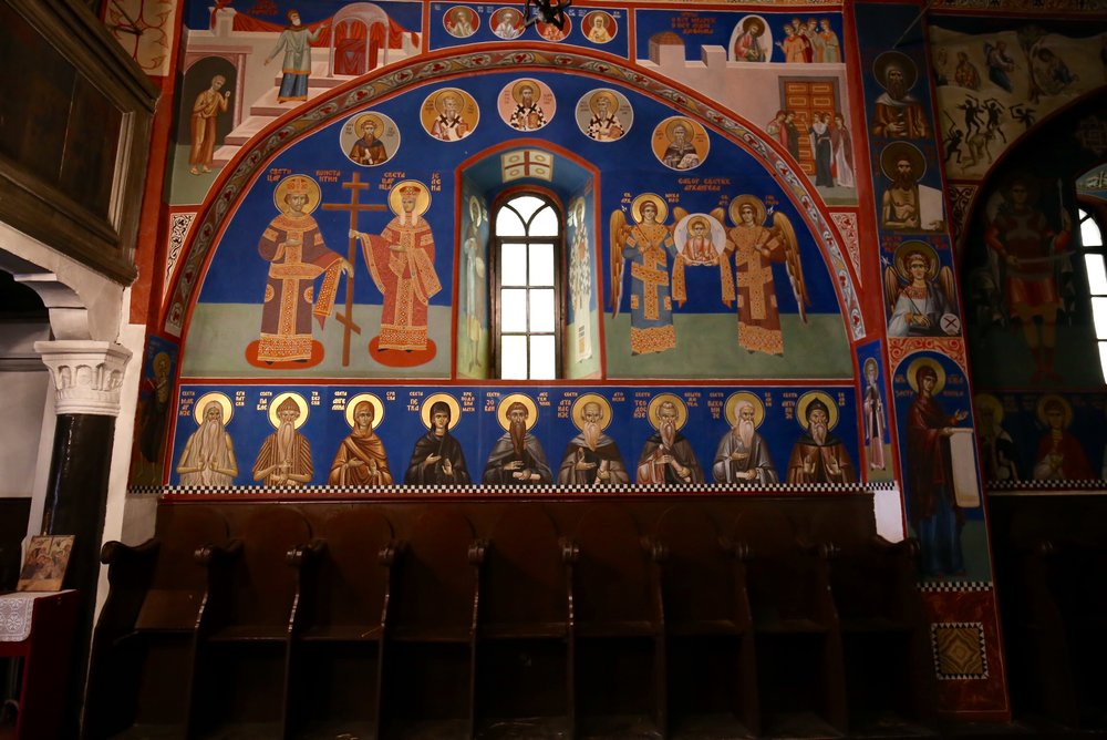 Paintings of saints, icons and angels in primary colours inside the dark church.