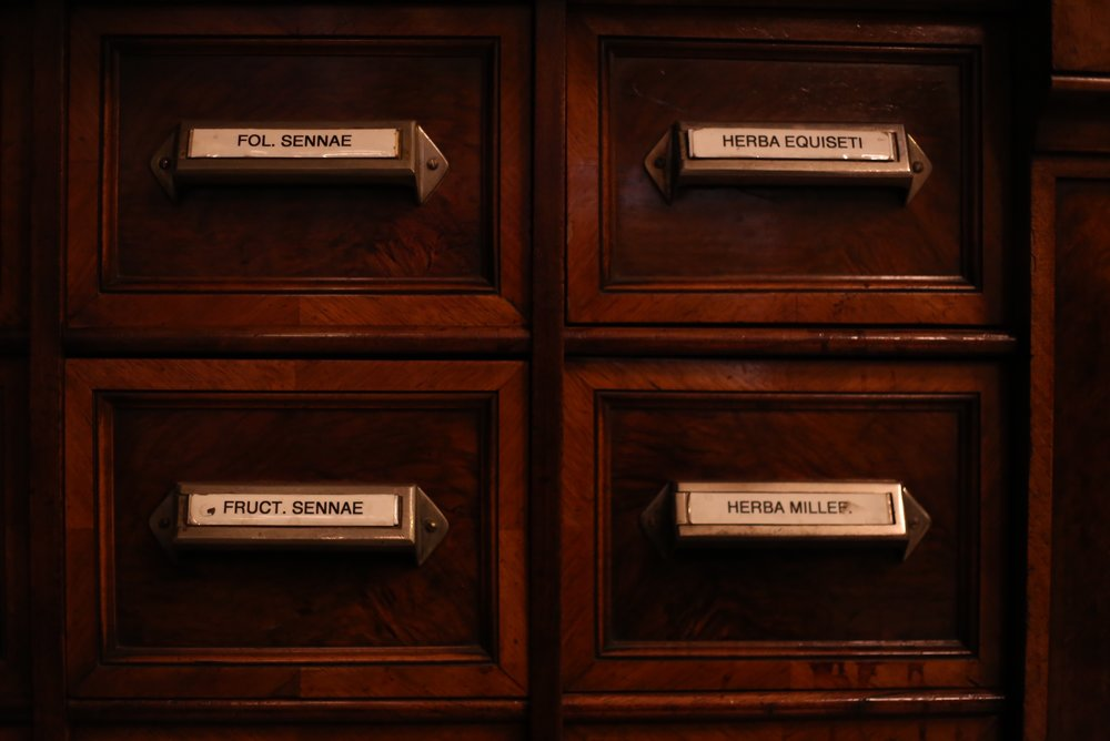 Wooden apothecary drawers with latin labelling.