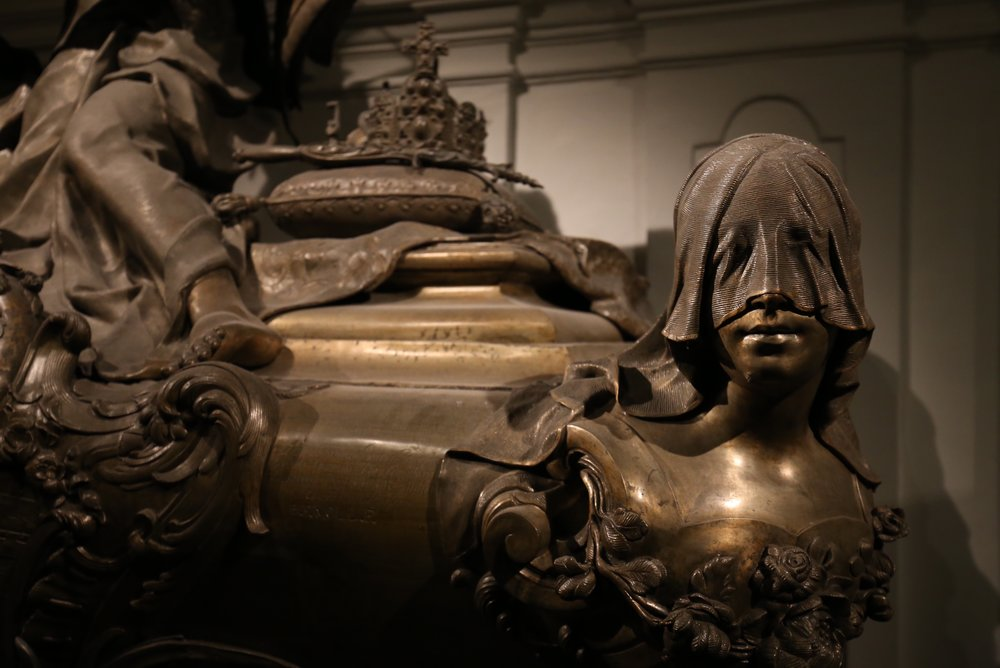 A veiled head looks out from a royal tomb.