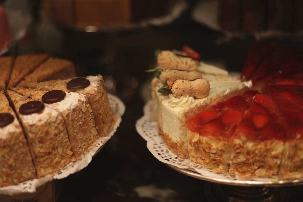 Fancy cakes set on stands in an old cake shop.