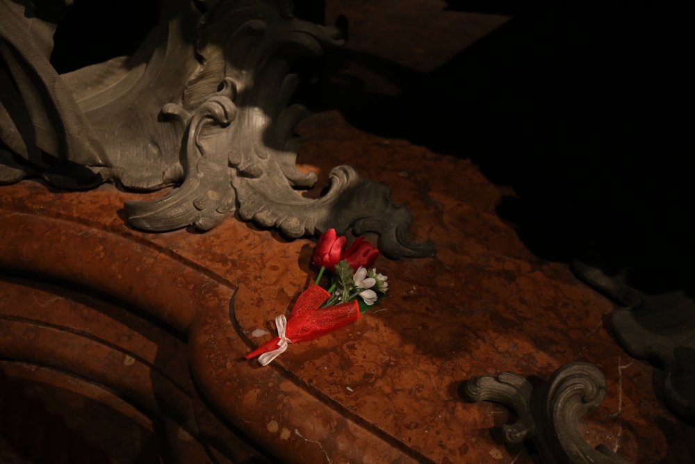 A small red bouquet laid on a grand tomb