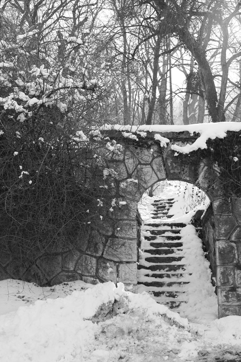 Stone stairs under an arch in the snow.