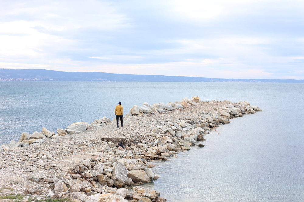 Oliver walks out on a white rocky pier by the ocean in Croatia.