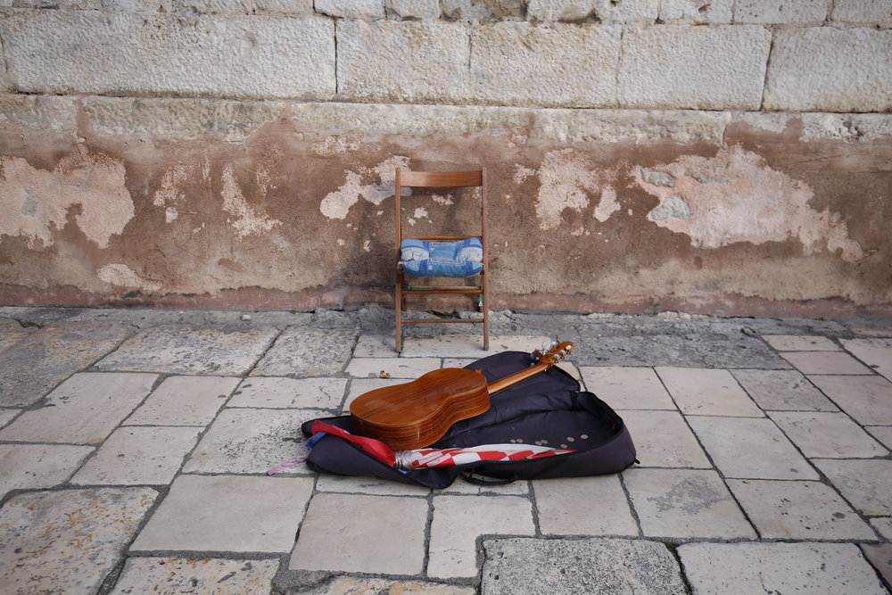 Guitar sits by an empty chair, the busker has gone for his lunch break.