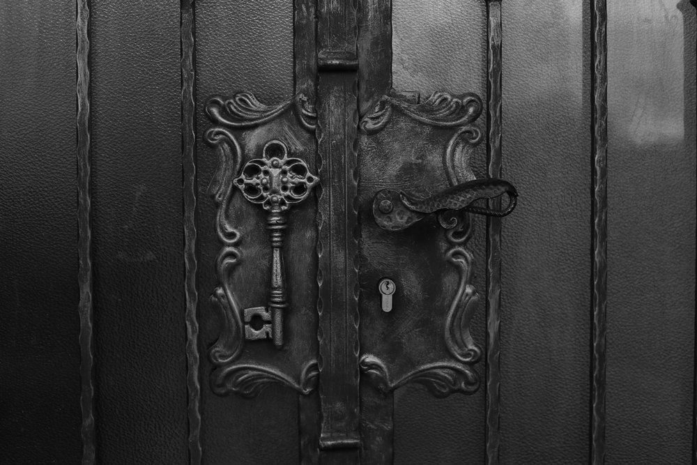 Door handle and brass key in black and white.